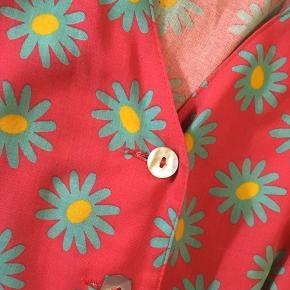 Vintagekjole i magenta med blomstermønster. Den har små/tynde skulderpuder og bindes bagpå 🐸