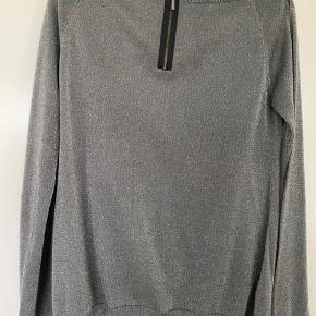 Meget elegant grå/sølvnistret trøje fra Babara Bui. Har flere fine detaljer med bindebånd ved halsen, små knapper der kan åbnes på hver skulder samt fin lille lynlås øverst bagtil.