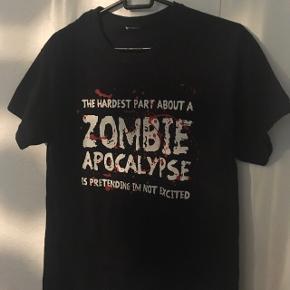 """#30dayssellout Den absolut fedeste sorte t-shirt med print/merchandise t-shirt med zombie quote """"The hardest thing about a zombie apocalypse is pretending I'm not excited"""" (true though 😂), købt på nettet, størrelsen har jeg klippet ud men mener det er en str M/38, unisex design. 🧟♀️🧟♂️  Kan passes af flere forskellige størrelser, alt afhængig af hvordan  man gerne vil have den skal sidde.  Sælges da den desværre er for stor til mig.   Har kun brugt den få gange, derfor er standen næsten som ny, ingen slid og intet af printet/teksten er afskallet! 😊  Købt til omkring 200-250 kr.  Hvis den skal sendes, betaler køber fragt.  Mvh Betina Thy"""