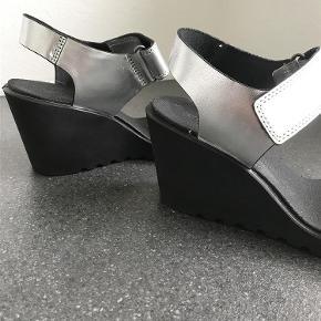 Varetype: Sølvsandaler Farve: Sølv, sort. Hæl bagpå 8 cm. Forfod 1,5 cm. Oprindelig købspris: 749 kr. Kvittering haves.  Brugt 2 gange, ingen slid eller skrammer. Velcro.
