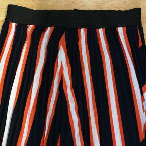 Plisseret, lang nederdel i mørkeblå, orange og hvid. Fra soya concept og kostede 500 fra ny. Aldrig brugt