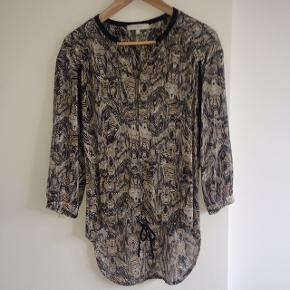 Fin feminin skjorte fra IRO. Str 0 i IRO - passer str 36. Løst fit, længere bagpå og med hæftelukning foran. Lækkert tyndt materiale 92% silke, 8% elasthan.
