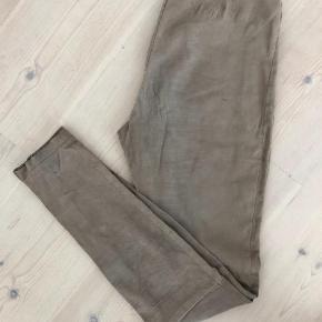 Varetype: Leggings Farve: Nude Oprindelig købspris: 7000 kr.  Smukke ruskindsleggins fra Utzon med pyton-præg og lynlås ved anklerne, med fast linning og lynlås bag på.