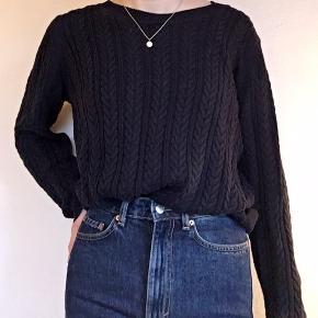 Fin mørkeblå sweater med fletværk foran og glat strik på bagsiden.