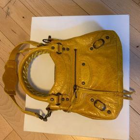 BYD  Super cool lille/mini Balenciaga skuldertaske sælges.  Model: Balenciaga Sac Classique Mini  Farve og materiale: Marigold Chevre Goatskin  Mål: h=16 cm., b=20 cm., bund=4 cm.  Kvittering, dustbag og æske medfølger.   Meget intakt taske. Stort set ikke brugt. Eneste brugstegn er på de små remme/stropper, som spændet på skulderremmen sidder i. Skriv for billeder😊