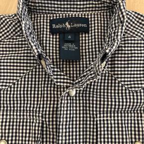 Fin blå- og hvidternet skjorte fra Ralph Lauren str 4 år. Rimelig stor i str. med trykknapper.  Fra dyre- og røgfrit hjem. Sender gerne med dao eller post nord. Prisen er plus porto.