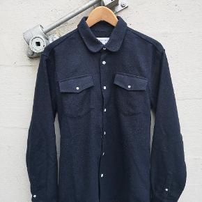 Lækker skjorte i uld som både kan bruges som skjorte om vinteren, samt som overskjorte/let jakke om sommeren. Navy blå. Skjorten er velholdt og pæn, og det er str. M hvilket passer mig perfekt (jeg er 185cm).