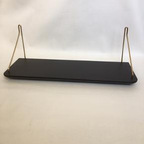 Retro hylde med sort linoleum samt holdere af 6 mm massivt messing. Messing skruer og messing skiver til ophæng følger med. Mål: længde 70 cm, bredde 24 cm, tykkelse 2,5 cm. Hylden har en god dybde til bøger. Hylden er super flot, nyistandsat, i perfekt stand  og lige til at hænge op. Kan sendes med GLS, eller hentes på Amagerbro i København. Tlf. 30206491