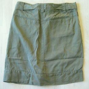 Varetype: Olivengrøn nederdel med bindebælte Farve: Olivengrøn   Olivengrøn nederdel med tryklåslukning, der skaber læg foran, og bindebælte.   Livvidde knappet ca 2 x 47 Længde ca 55 cm  Jeg bytter ikke !  Byd gerne samlet på flere annoncer, så sparer du porto og jeg kan give dig rabat :-)