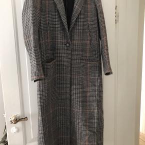 Lang, elegant uldfrakke, som falder utrolig flot. Den er let og blød og egner sig godt til forår og efterår, da den er uden for.  Kan ses/hentes/prøves på Østerbro.