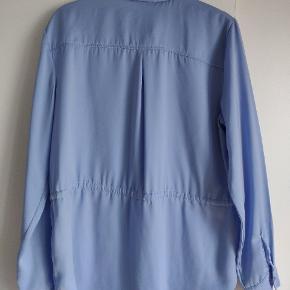 Varetype: Skjorte  Farve: Lyseblå   Knapper, også ved enden af ærmerne, kan strammes ind ved taljen
