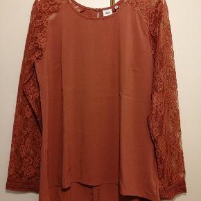 Fin bluse med gennemgående blonde langs ærmerne. Blusen har aldrig været brugt og prismærke sidder stadig på.