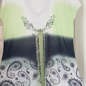 Top med blondedetalje og v hals i 35% Bomuld/65% Polyester. BM: 2x51cm Længde: 63cm Talje: 2x47cm