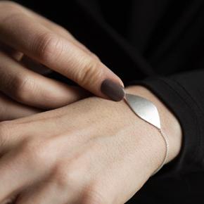 NYT sølvarmbånd i æske (posen er gået i stykker) Den danske smykkedesigner Louise Kragh har lavet Leaf serienArmbåndet har en smuk form, som er let og elegant og er perfekt til at kombinere med andre armbånd eller lade skinne selv * Louise Kragh smykker laves i materialer, som udvælges med stor omhu * Louise Kragh smykker anvender udelukkende sterling sølv 925 * Smykkerne designes og produceres på værkstedet i Danmark Leaf armbåndet er i sterling sølv 925Armbåndet er justerbart i længderne 16/17/18/19 cm Nypris 599 kr. Fået i gave uden byttemærke  #Sølv sølvsmykker sølvarmbånd smykker armbånd student konfirmation leaf blad louisekragh accessories danishdesign smykkedesign 925 925s