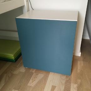 Fint Ikea Bestå skab med 2 hylder og petroliumsblå låge. Kan hænges på væggen eller stå på gulvet. Har mindre brugstegn. Fra hjem uden røg og dyr. Afhentes i Farum. Højde 64 cm Bredde 60 Dybde 40 cm