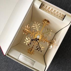 Smuk Royal Copenhagen topstjerne.  Aldrig brugt og stadig i original emballage, og fremstår derfor som ny. Der medfølger spiral og snor, så den både kan hænge eller sættes på juletræet.  Farve: belagt med 24 karat guld Højde: 23 cm Bredde: 22 cm Model: ikke længere i produktion    SÆLGES FOR 4000 KR. (Prisen er fast)   (Sælger også et originalt Royal Copenhagen juletræstæppe)
