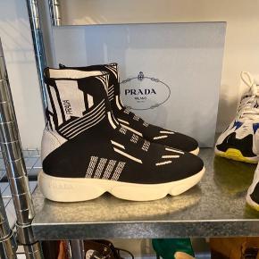 ‼️FAST PRIS! Læs venligst hele teksten inden spørgsmål‼️  Fede Prada Nylon Tech sneakers med print. Brugt 3 gange, men må desværre erkende at de er lidt for store (bruger normalt 38). Intet tegn på brug udover på bunden af skoene.  Str. 38,5. Normale i størrelsen, kan dog også gå til en 39.   Købt i Italien. Har ikke gemt kvitteringen. Der medfølger æske samt dustbags. På æsken står original prisen €650 hvilket svarer til ca 4.850 danske kroner. Står inde for ægteheden og handler gerne over Trendsales handel så køber har garanti. Ellers kan de hentes i Ørestad Syd på Amager.   Bemærk at de også er sat til salg på Vestiaire Collective.