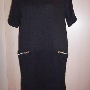 Brand: ZbyZ  Str. S ( M/L)  (SPAR kr, 270,-)Varetype: Tunka/kjole  KUN 129,- m fine pynte lynlåse  m Label Farve: Sort Oprindelig købspris: 399 kr.  Sød sort kjole med flot rund halsudskæring og korte ærmer. Midt foran har den 2 dekorative pynte lynlåse og fra lynlåse og ned -KUN FORAN, er stoffet vendt på vrangen, hvilket giver en flot effekt. Det kan anes på foto 4.  Brystvidde: 112 cm Længde: 85 cm  100% Polyester.  Sælges ny og ubrugt og stadig med prismærke.