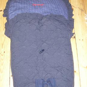 Super fin kørepose fra italienske Peg Perego.  Er mørkeblå med hvide prikker og har mørkeblåt blødt fleecefoer.  Kan lynes helt op, så det kan bruges som tæppe. der er huller til sele
