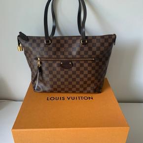 Sælger min Louis Vuitton Iéna MM i Damier Ebene.  Jeg har købt tasken i LV butikken i Kbh.  Jeg har ikke brugt den så ofte og er meget velholdt. Den har været opbevaret i stofpose i æsken for det meste.  Der er en mørk plet (muligvis fra parfume) i det store rum og en lille plet (læbepomade) i det lille rum. Se billeder. Disse kan højst sandsynligt fjernes.  Der medfølger følgende:  - æske - stofpose - kvittering  Denne taske er en udgået model.  Nypris (inden den udgik) ca. 10.000 kr.  Sælges til 6.700kr.