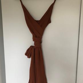 Er aldrig blevet brugt. Selvom den er en str. 38, så passer den nok bedre en str. 36. Der er lynlås på ryggen og bånd der kan bindes rundt om taljen, så kjolen bliver super feminin.