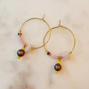 Forgyldte håndlavede kreoler med rosakvarts, farvede glasperler, forgyldte perler og vedhæng af mauve ferskvandsperle. 25 mm i diameter. Nikkelfri.