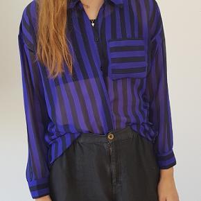 Fin let skjorte i kunststof. Oversize i snittet så passer også en medium.
