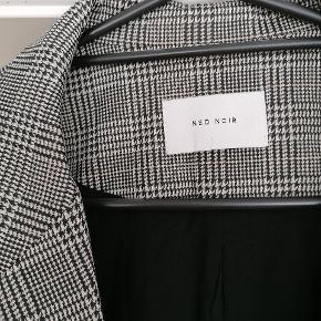 Fineste sort/hvid ternede blazer fra Neo Noir str. L, svarende til ca. 40. Den har bare været på en enkelt gang og fremstår helt som ny...  Sælges da den desværre ikke passer mig helt perfekt.  Så lækker kvalitet og snit!