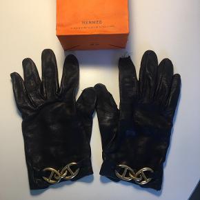 """Hermes/Hermés/Hermès – Handsker.  Beskrivelse:  - Sort lammeskind med guld """"Chaine d'Ancre""""-spænder. - Str.: Huskes som 7,5. - Medfølger: Pose. - Slidte! Kan evt. laves til fingreløse handsker el. spænderne kan tages af og bruges som smykke.  NUL BYTTE - FAST PRIS!"""