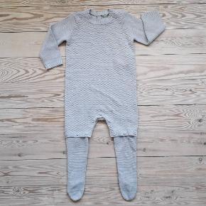 Grå heldragt i strik fra Benetton Baby, str. 74. Med trykknapper forneden og aftagelige ben/strømper. Kun vasket og brugt en enkelt gang - ser ud fuldstændig som ny. Pris: 75 kr. plus porto