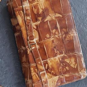 Varetype: Clutch Størrelse: 25×17 Farve: Brun  Vintage clinch I krokodilleskind. Der er et udvendigt og 4 indvendige rum. Foret er satin. Formentlig fra ca 1940