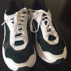 Fede sneakers fra Puma i deres cell model. De er sorte/hvide/mørkegrønne. Kun brugt få gange