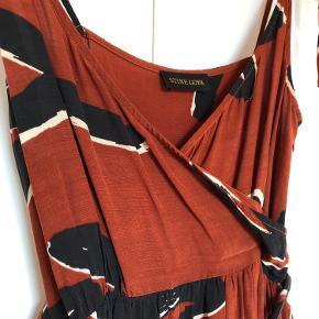 Smuk mønstret kjole med slå om effekt og bindebånd på skuldrene. Virkelig flot men desværre for lille til mig, så brugt meget sparsomt. Kan afhentes i Aarhus eller Vejle efter aftale :)