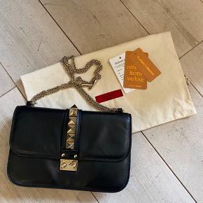 Valentino Glam Lock lædertaske i str medium.  Tasken er i fin stand. Dustbag og kasse følger med, samt tags fra Vestiare Collective hvor den er købt i januar 2019 for 8.000kr. Nypris er 13.500 kr. Læderet er behandlet for nyligt.  Bytter ikke. FAST PRIS.