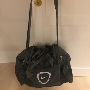 Nike sportstaske i grå inkl. skulderrem. Brugt 1-2 gange, står som ny. Tasken har et stort rum og mindre rum i enderne.