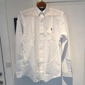 Hvid Slim Fit skjorte fra Polo Ralph Lauren, str. L. Aldrig brugt, stadig med prismærke. Bytter ikke og prisen er fast. Opr. pris: 800,-  Pris: 300,-
