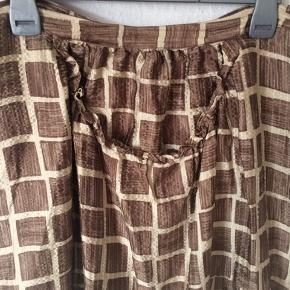 Rützou - silke nederdel Str. 42 Næsten som ny Farve: brun ternet Lavet af: 95% silk og 5% spandex Har en stor lomme foran Mål: Livvidde: 92 cm hele vejen rundt Længde: 72 cm Køber betaler Porto!  >ER ÅBEN FOR BUD<  •Se også mine andre annoncer•  BYTTER IKKE!