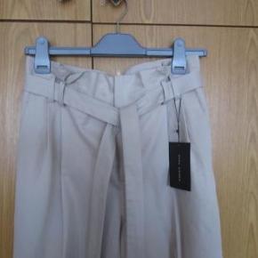 3/4 bukser aldrig brugt, købte dem uden at prøve dem i London. Da jeg kom hjem kunne jeg se at de ikke er lagt op i den ene side. De har normalt et lille opslag på buksebenene.
