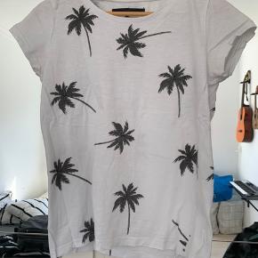 Hvid t-shirt med sorte palmer, brugt men i god stand. Sælges billigt da jeg ikke kan passe den mere.