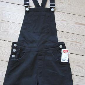 Sorte shorts-overalls fra H&M, str. 13-14 år. Aldrig brugt. Stadig med mærke. Sælges for 60 kr. + porto, men KUN via Mobilepay.
