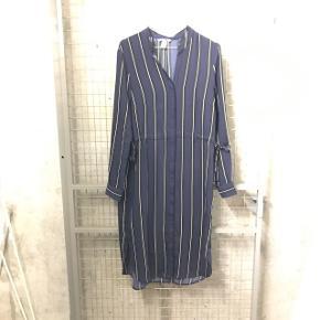 Mørkeblå kjole med sorte og hvide striber.  Bindebånd i begge sider af taljen. Trykknapper i ærmets manchet. Knælang. Har en plet, som næsten ikke ses i dagslys.