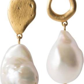Fine ægte perleøreringe fra Enamel i forgyldt sølv med ægte ferskvandsperler. Meget populære øreringe.  Smukke øreringe med en helt unik barok ferskvandsperle. Øreringene er elegante og tilfører den smukkeste detalje til dit look. Idet perlen er unik, kan størrelse og formen variere, hvilket blot gør dem virkelig smukke og specielle.  Mål: L 3,5 cm   Materiale: 18 karat guldbelagt sterling sølv.  Nye og ubrugte. Nypris i butikker 800 kr.  Sælges for 550 plus porto. Sender kun i DK.  Betaling mobilpay eller kontant.  Prisen er fast. Bud under 550 kr besvares ikke. Sender ikke private billeder, hvor jeg bærer øreringene.     Jeg bytter ikke.  Kommunikation: DK