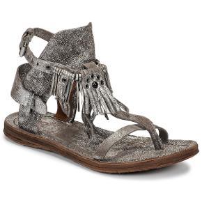 Ny skind sandal i silver farve i normal str. 36 købt for kr. 1.350,- Desværre har den en lille skade på stroppen bagpå, et lille hak i stroppen, men den sidder fint og kan sikkert fixes hos en skomager så derfor sælges sandalen billigt - har aldrig været brugt, sælges da jeg bare har for meget i skabet.