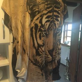 Lækker bluse med tigerhoved både for og bag i 95% polyester og 5% elastahan . Meget lækker og køber betaler Porto