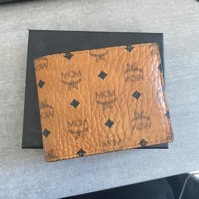 """Velholdt """"bifold wallet"""" i cognac farve (deres ikoniske farve)  Det er med en ekstra kort lomme, som vist på billedet - den kan tages ud hvis ikke ønskes i.  Rigtig fin stand - har box, kviterring og dustbag til den  Ny pris er ca 2000kr  Kan sendes eller hentes i Fredericia!"""