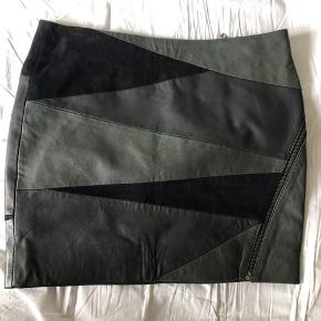 Fed lækker læder- og ruskindsnederdel! 😍. Sælges kun, fordi jeg ikke kan passe den. Aldrig brugt.  Den er lavet af sorte og mørkegrønne stykker af læder og ruskind. Virkelig blød!
