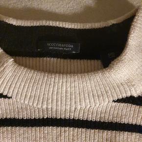 Sweater er laver af bomuld med stretch, den er let taljeret og kraftig i strikken.  Marineblå striber og kanter ved ærmerne og indersiden af kraven. Ca. 50 cm over brystet og godt 60 cm lang. Jeg har haft den på et par gange med t-shirt under. Ren, men aldrig vasket.