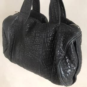 Smuk taske i sort lammeskind. Flot rå bund med markante nitter. Taskens mål er bredde 33, højde 23. Nypris 6.995,-