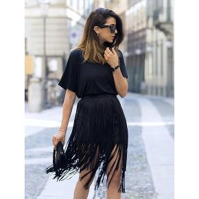 Tætsiddende nederdel med frynser. Frynser nogle cm længere end inderkjolen. Se 3. Billede