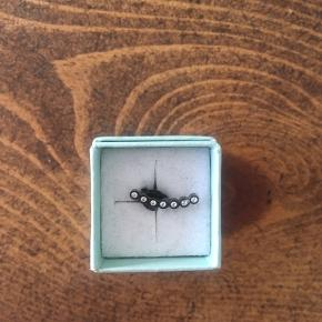 1 øreringe i modellen seven dots med syv zirkoner i oxyderet sterling sølv til venstre øre.